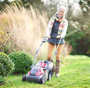 Woman mowing a lawn with a Mountfield Cordless Mower