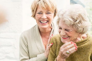 carer and elderly lady laughing