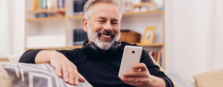 Smiling man sitting on sofa and looking at mobile.