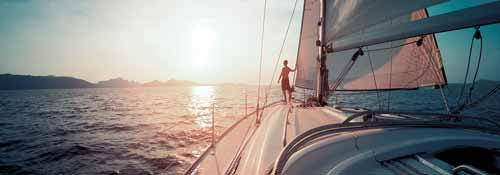 Man standing at the bow of a sailing yacht at sunset