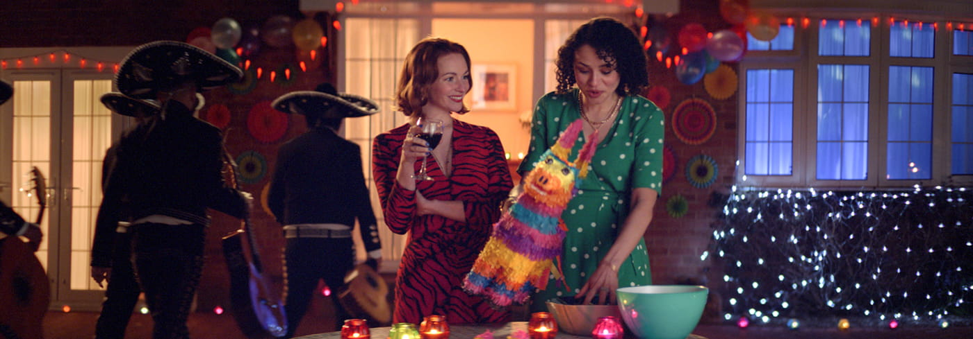 Two women chatting at a Mexican themed party