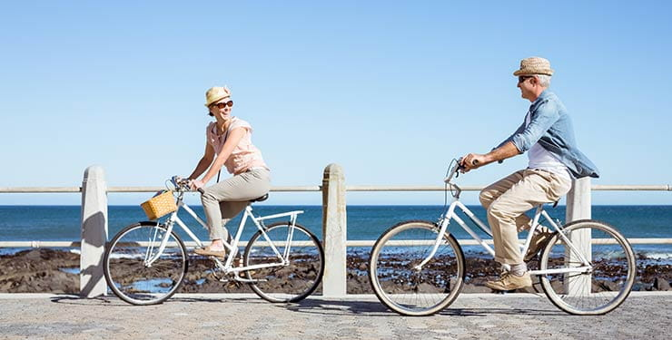 Woman and man riding bikes along the coast on a sunny day