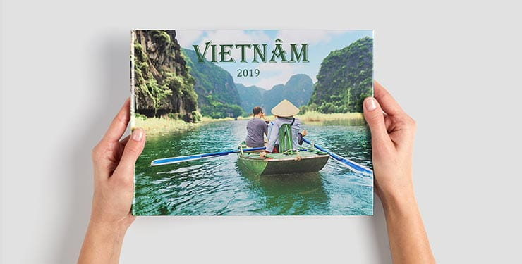Person holding a CEWE Photobook entitled Vietnam
