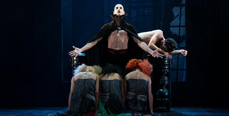 Northern Ballet's Dracula. Dracula stands while the Brides of Dracula kneel before him. Photographer Emma Kauldhar
