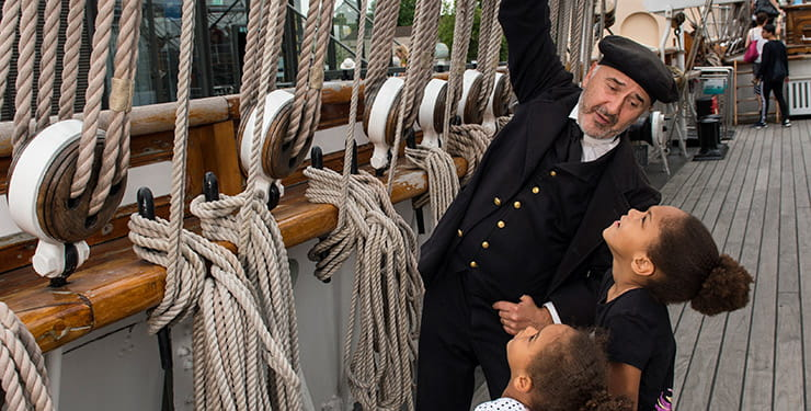 Cutty Sark sailor showing children the ropes. National Maritime Museum