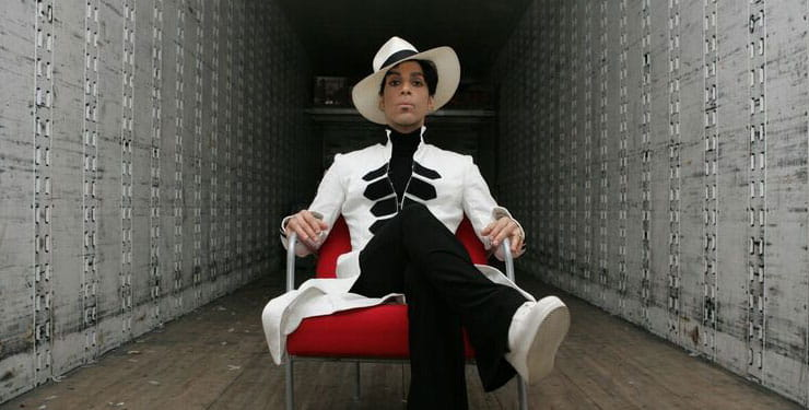The music artist, Prince, sits in a red chair wearing a white hat and suit