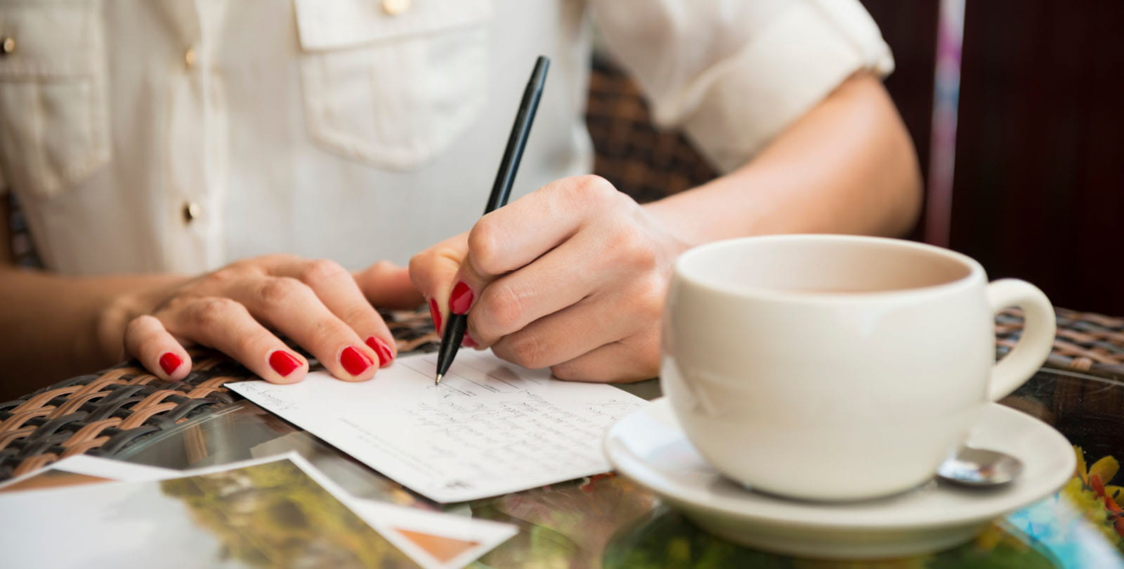 Woman sat at a table writing postcards.