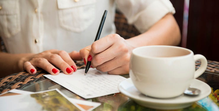 Woman sat at a table writing postcards