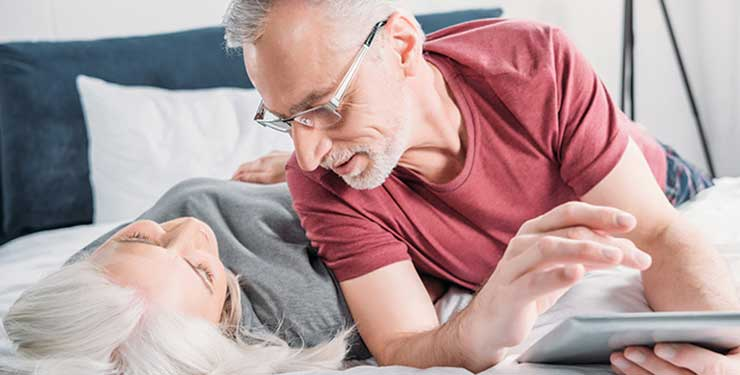 Chemist Direct: Couple on bed with laptop