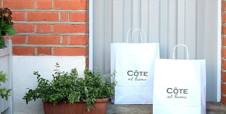Two Cote at Home shopping bags on a doorstep
