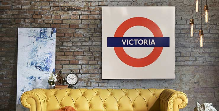 Vintage sofa and other products against a brick wall with a large Victoria line tube sign.