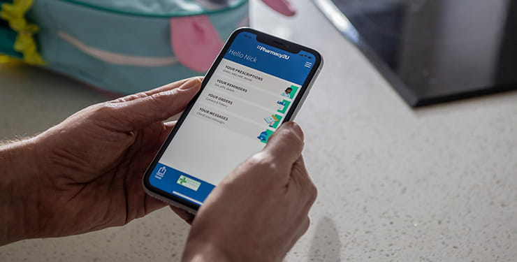 Hands holding a mobile phone that shows the Pharmacy2U app