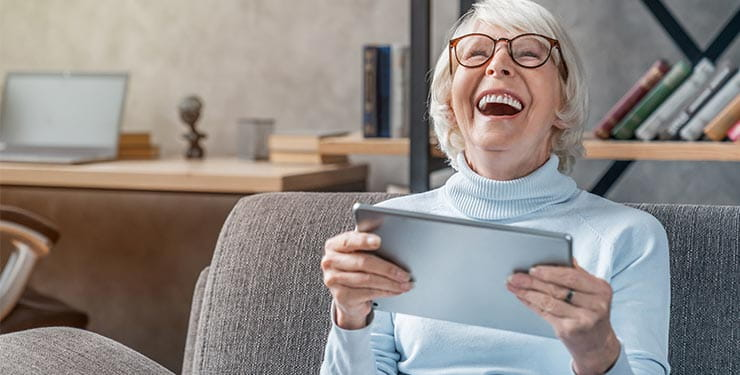Woman holding a tablet and laughing