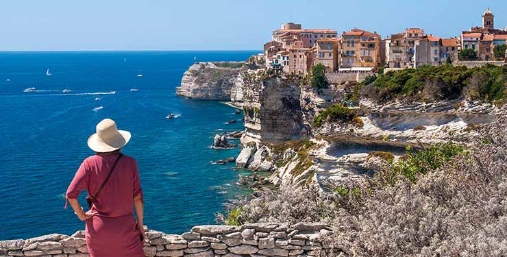 Person standing at viewpoint, looking at the city of Bonifacio, Corsica