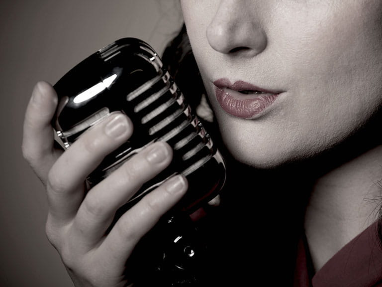 Woman with old fashioned microphone close up