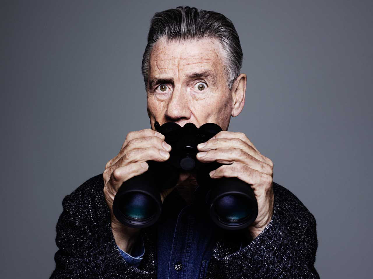Actor Michael Palin holds a pair on binoculars