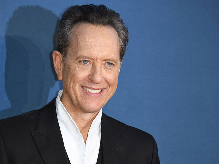 Richard E Grant poses for photos at his film premiere