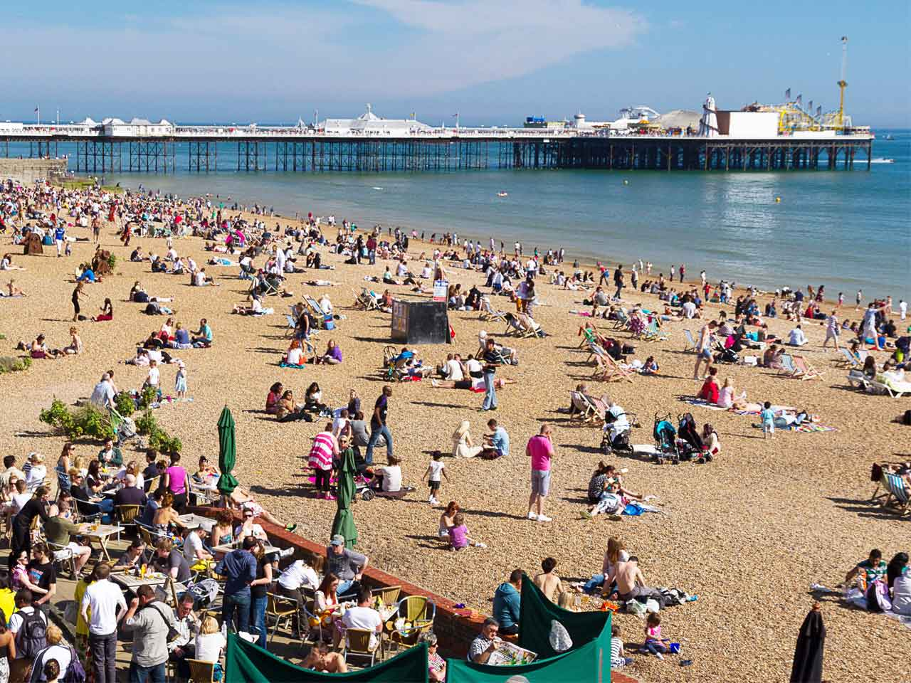 A busy Brighton beach and Brighton pier
