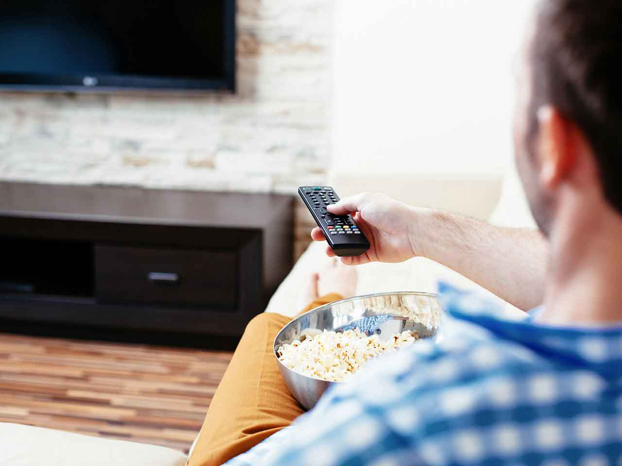 Man watching TV eating popcorn