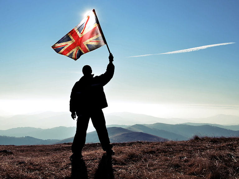 An older man waves a Union Jack from a mountain in silhouette