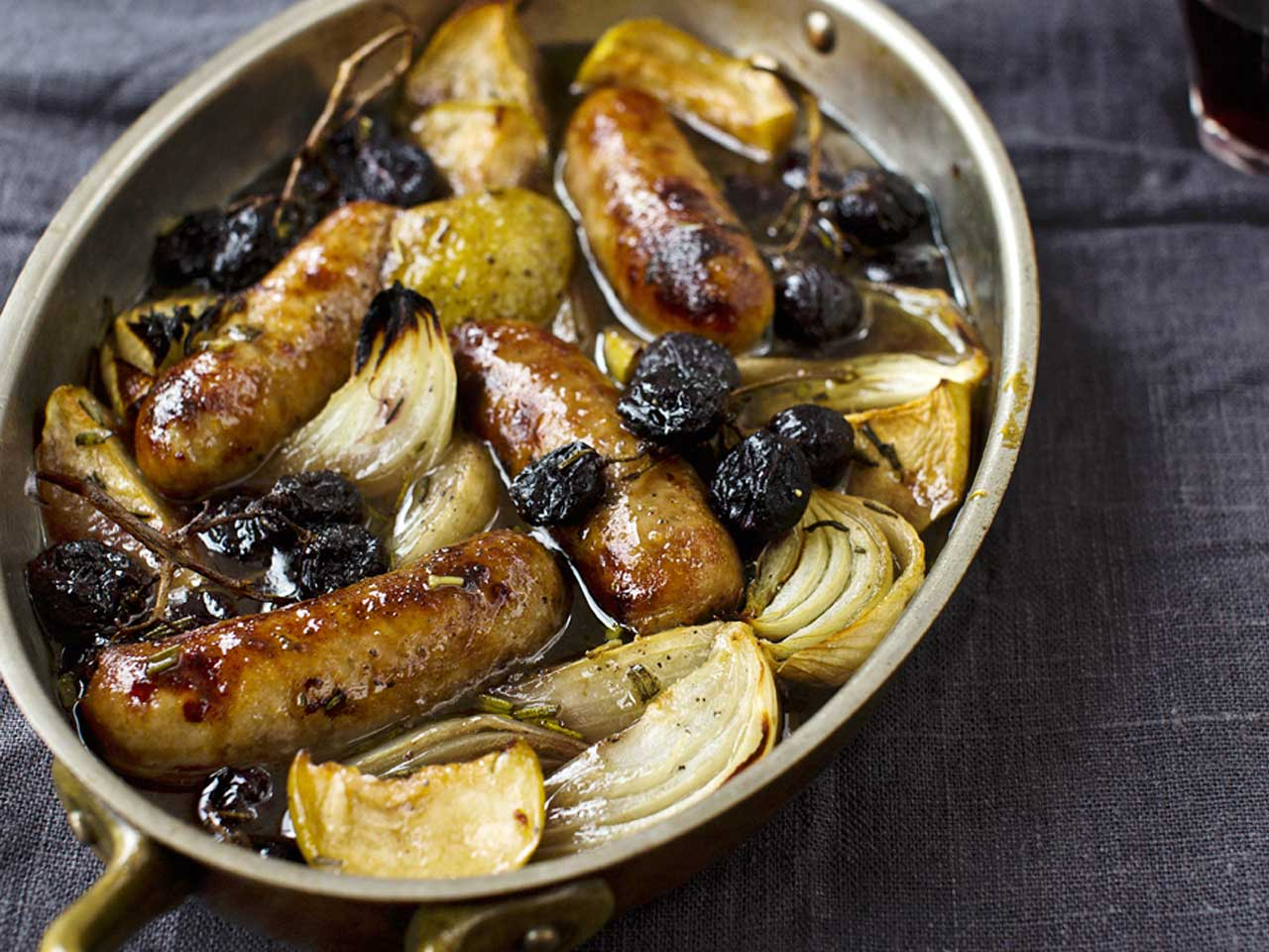 Sausages roasted with apples, grapes and sherry