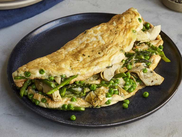 Soufflé omelette with asparagus, peas and artichokes