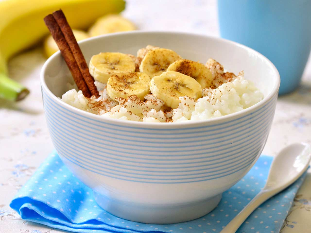 Bowl of porridge with banana and cinammon sticks