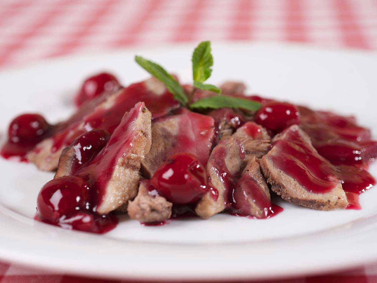 Duck breast with cherries on a place on table