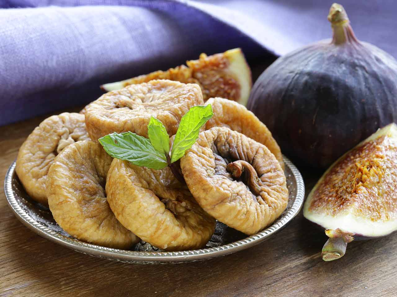 A plate of dried figs and a fresh fig