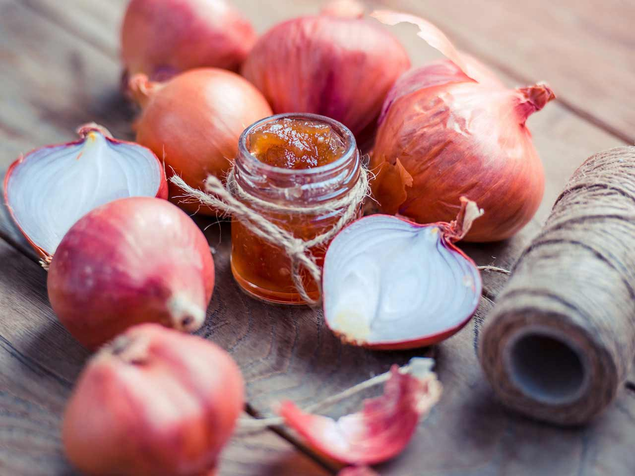 Onion marmalade surrounded by onions on wooden table