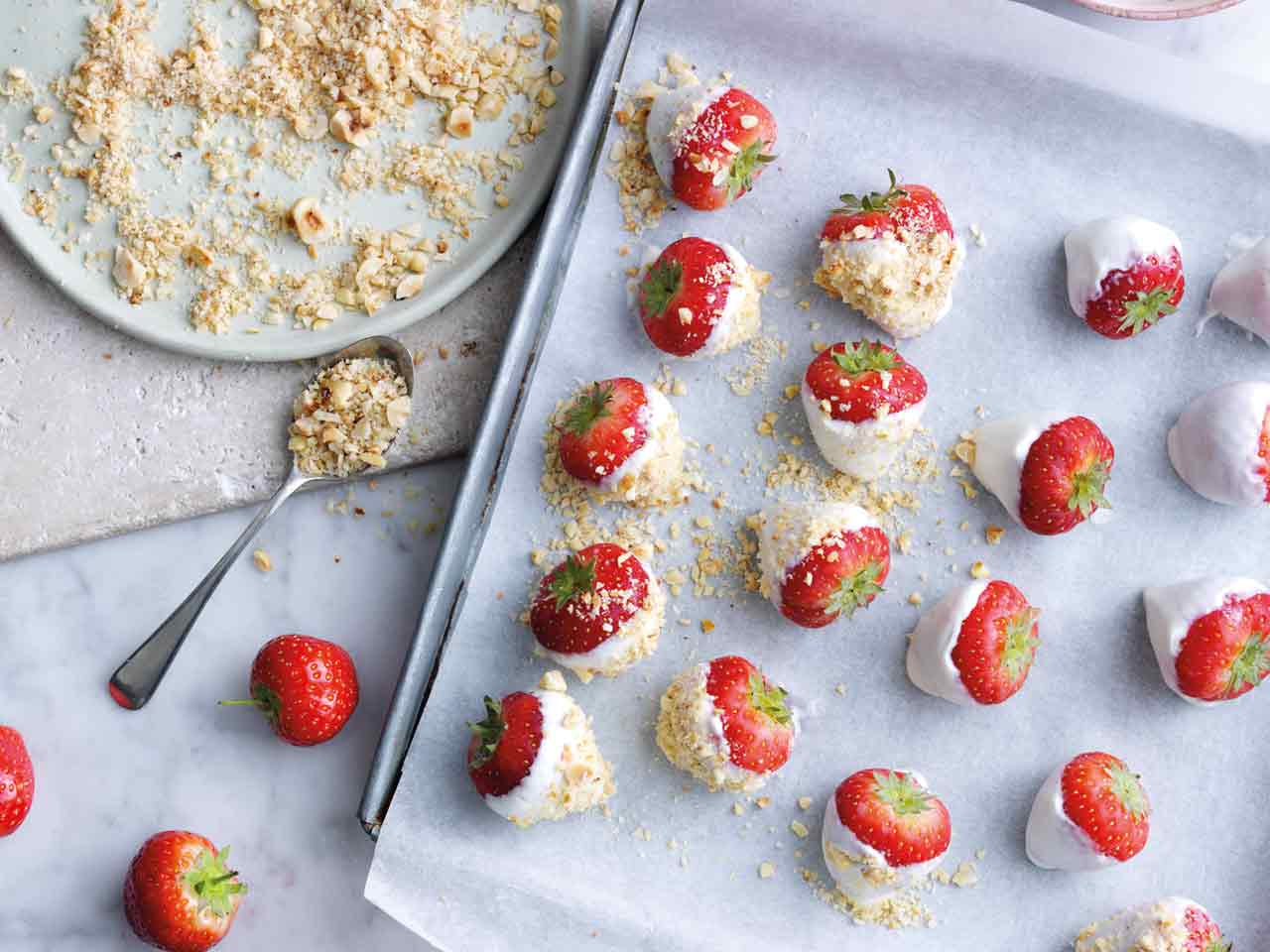 Strawberries dipped in yoghurt and hazelnuts