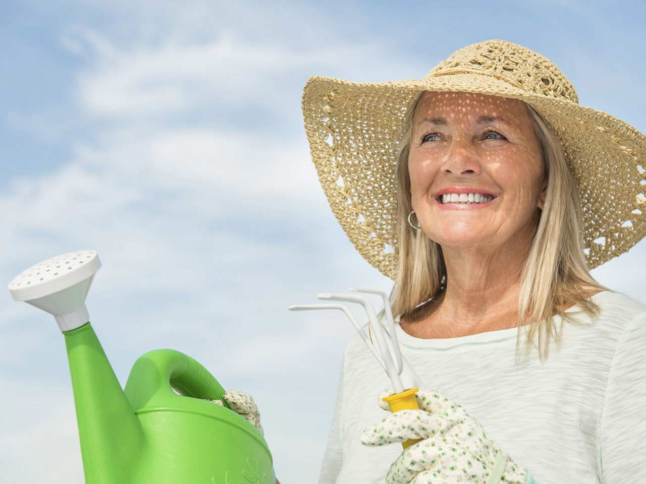 Senior lady gardening wearing sunhat for protection