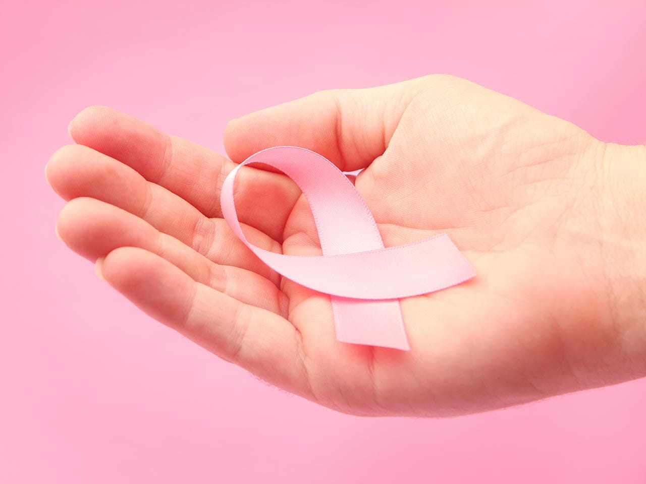 Hand holding breast cancer pink ribbon