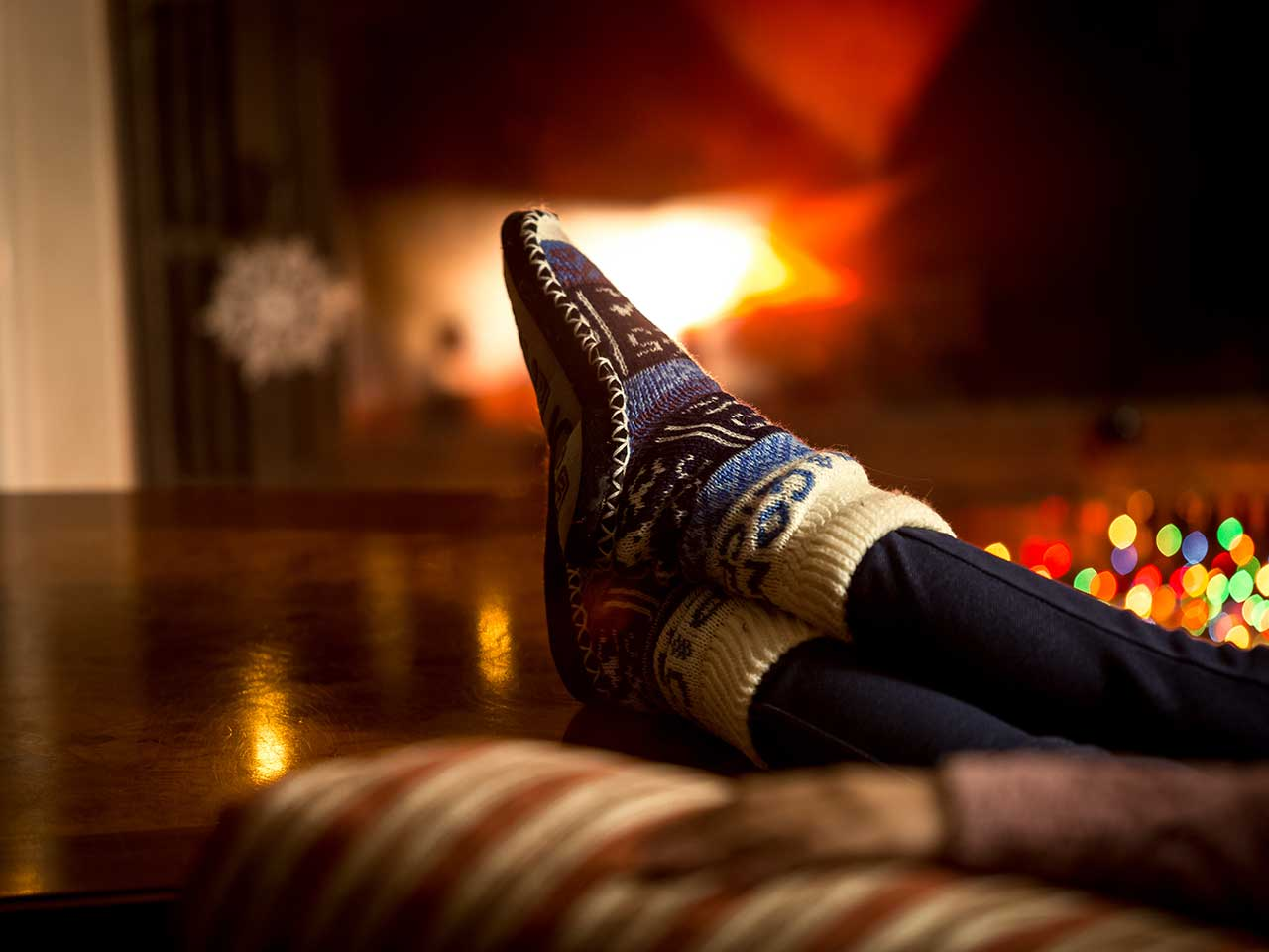 Slippered feet in front of warm fire at Christmas time