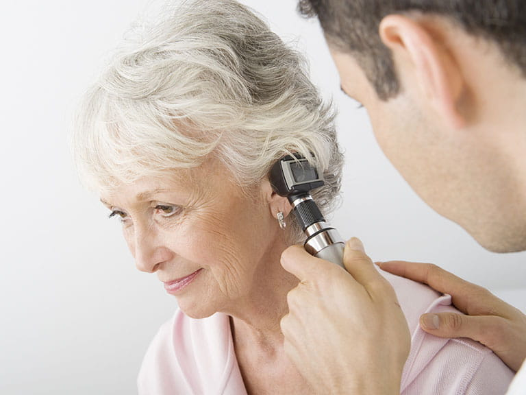 Doctor looking into senior lady's ears
