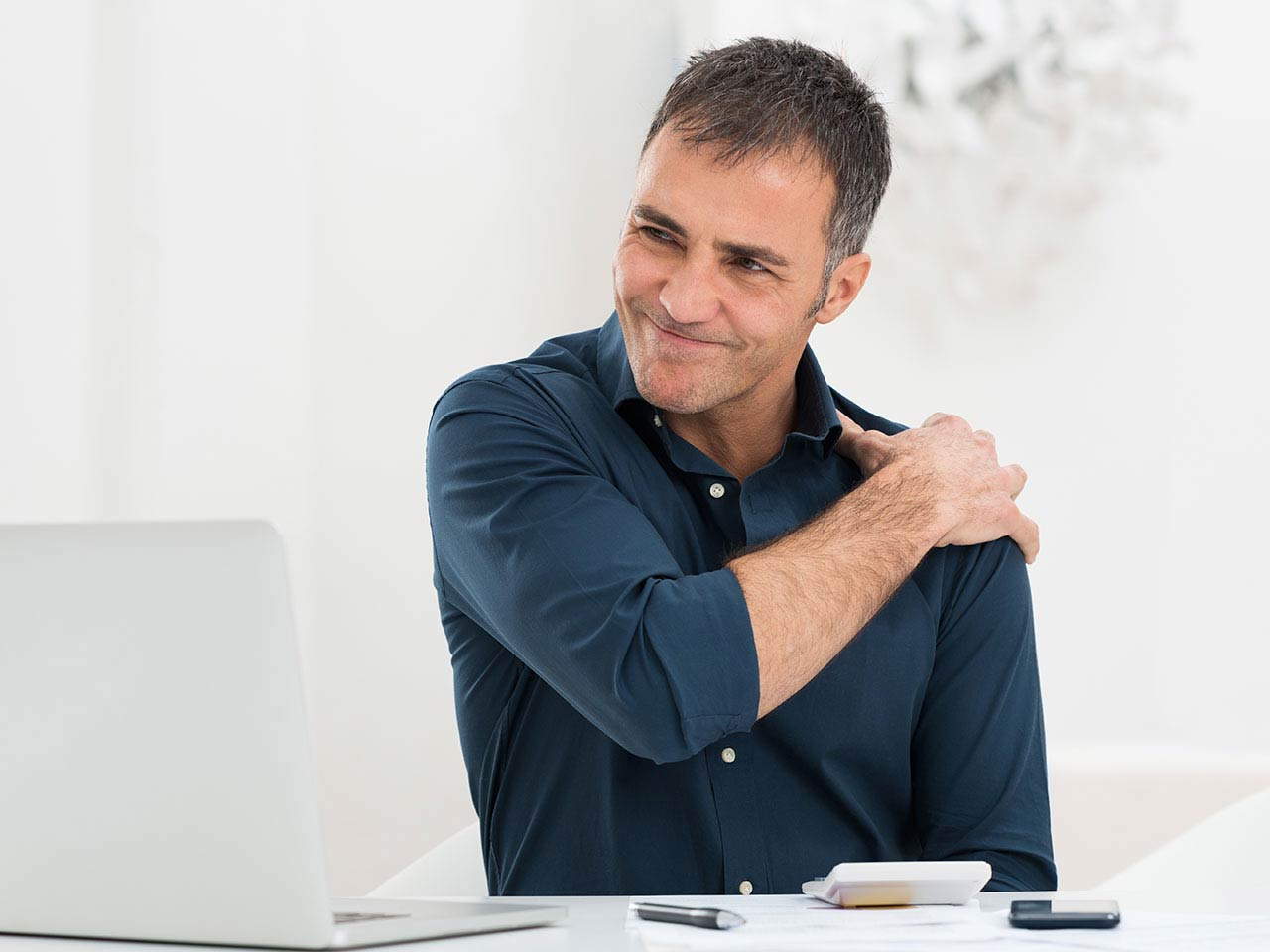 Mature man sitting in front of computer suffering shoulder pain
