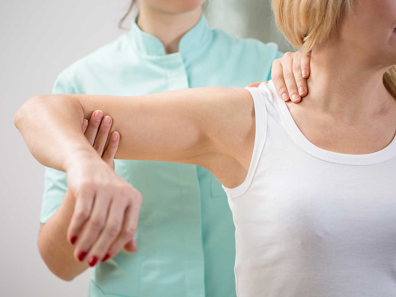 Woman with physiotherapist looking at shoulder