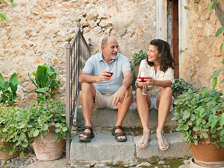 Mature couple sitting outside drinking wine