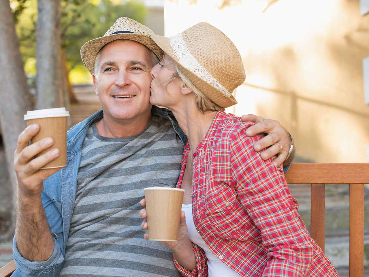 Mature couple sitting on a bench drinking coffee