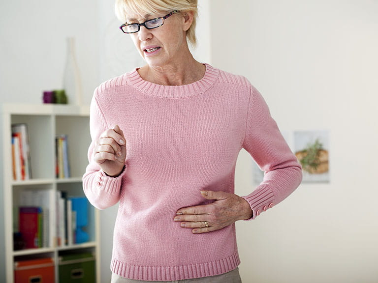 Senior woman holding abdomen in pain