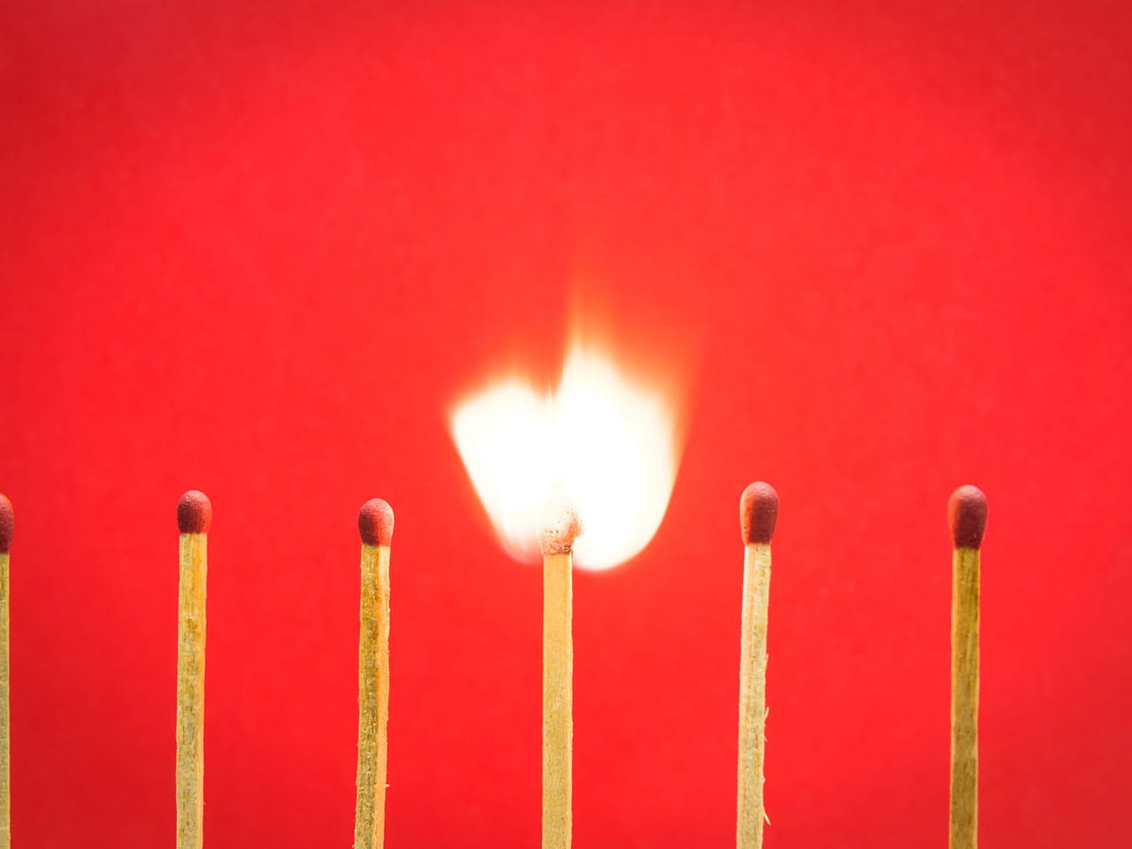 Burning match against red background referring to inflamed pain