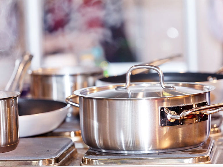 Steaming saucepans in a busy kitchen