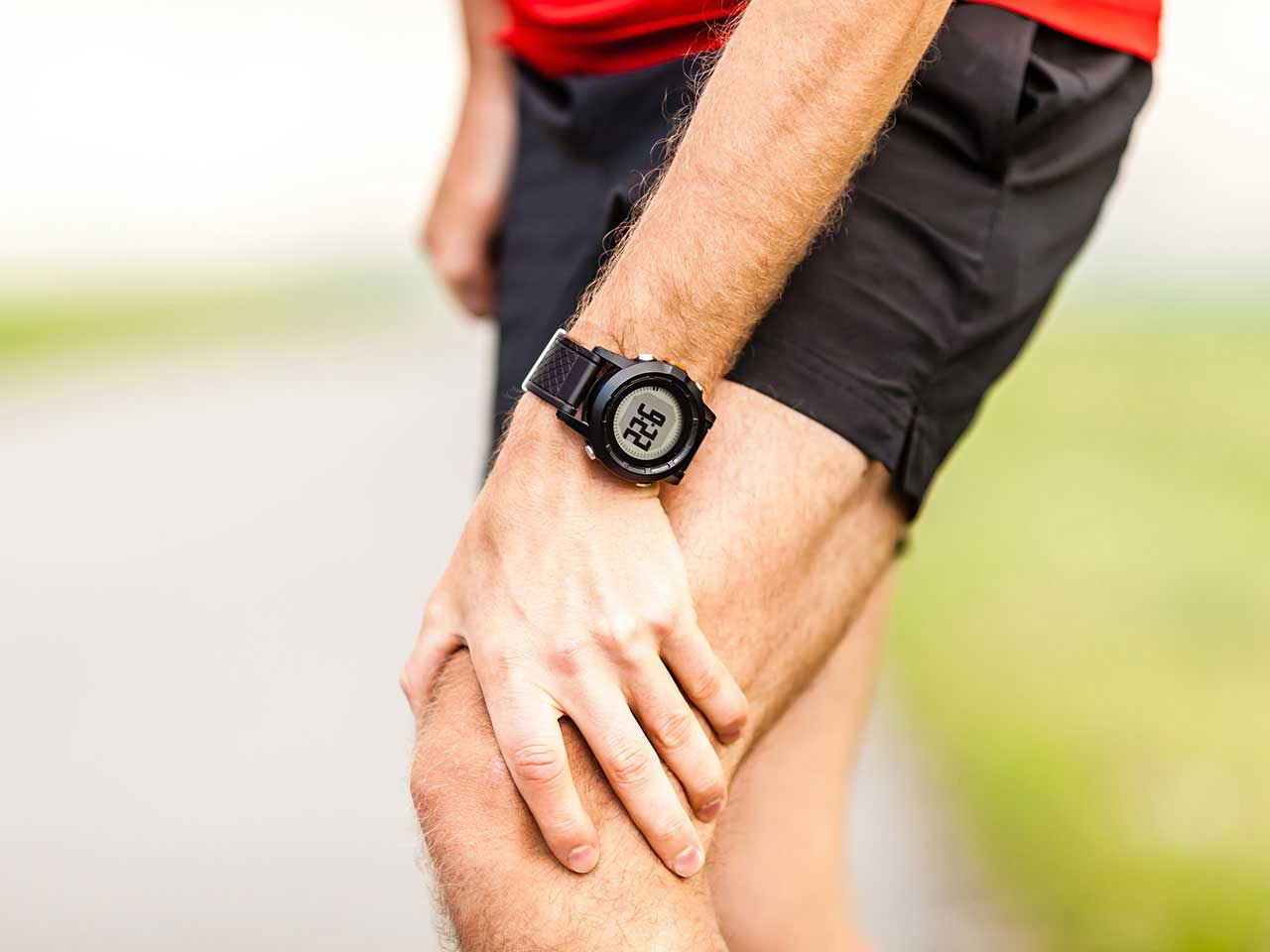 Male runner holding knee for pain relief