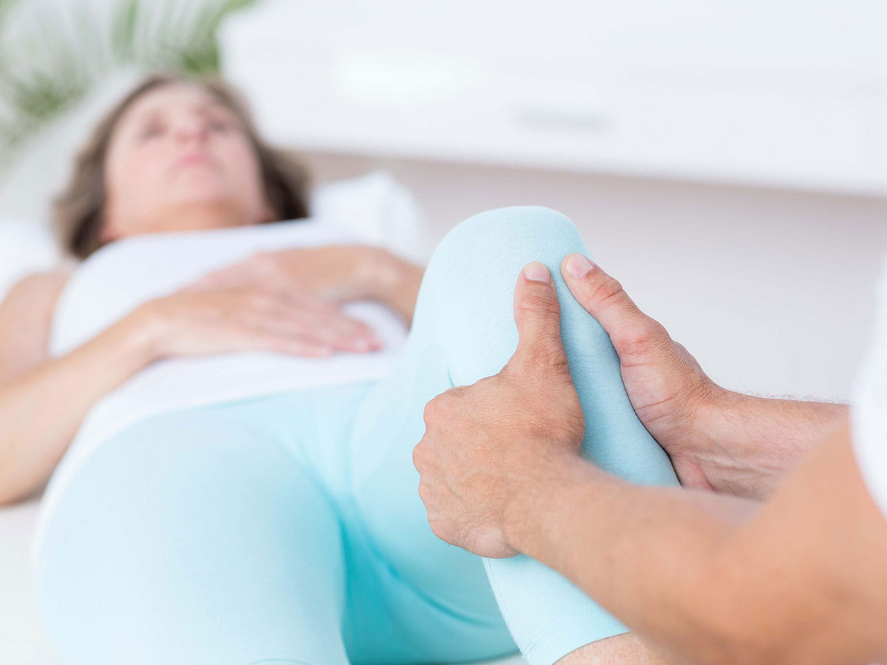Mature lady having physiotherapy on her knee