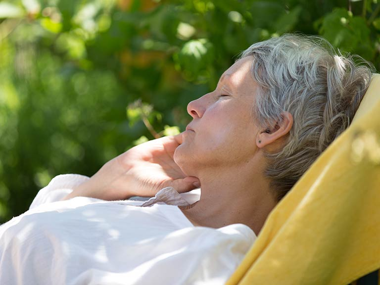 Mature woman asleep in a garden chair