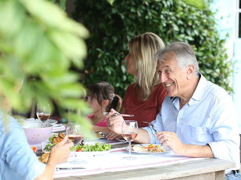 Senior couple eating with family in the garden