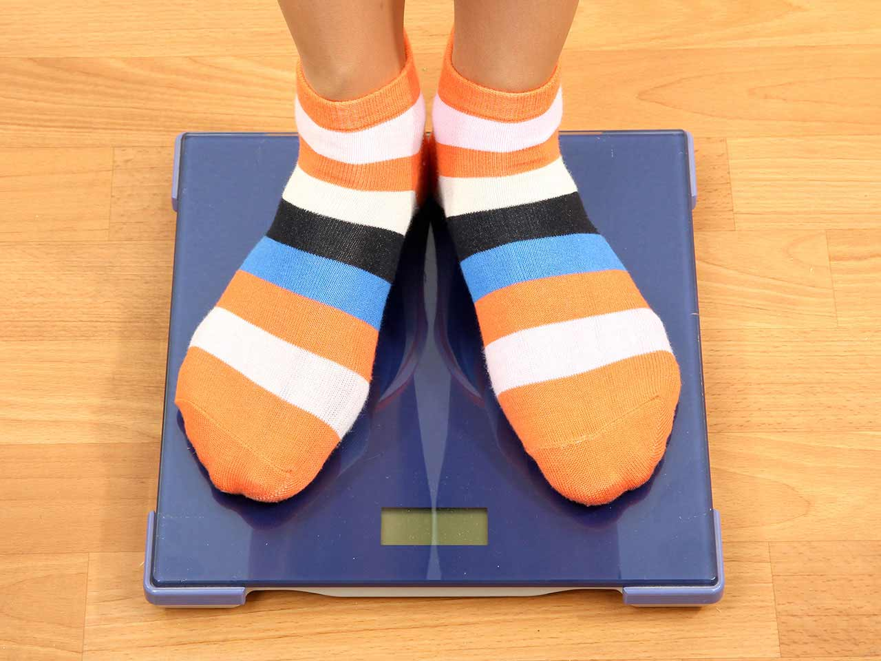 Person standing on bathroom scales in stripy socks
