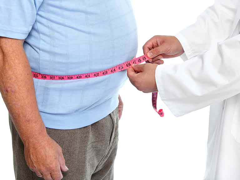 Overweight man having waist measured by doctor