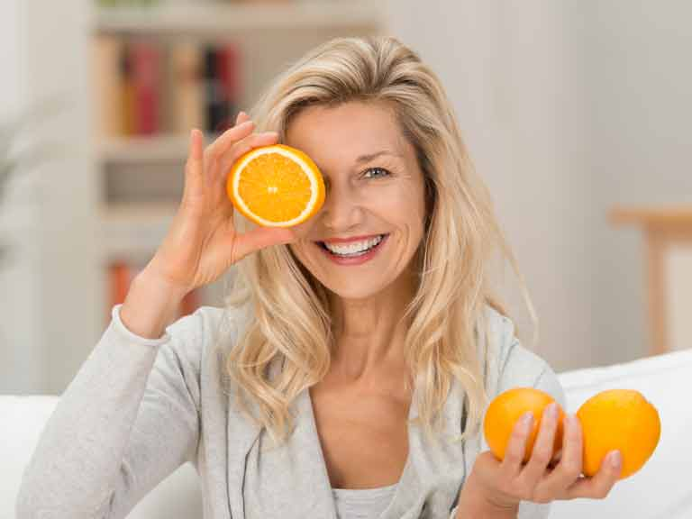 Woman with vitamin C-rich oranges
