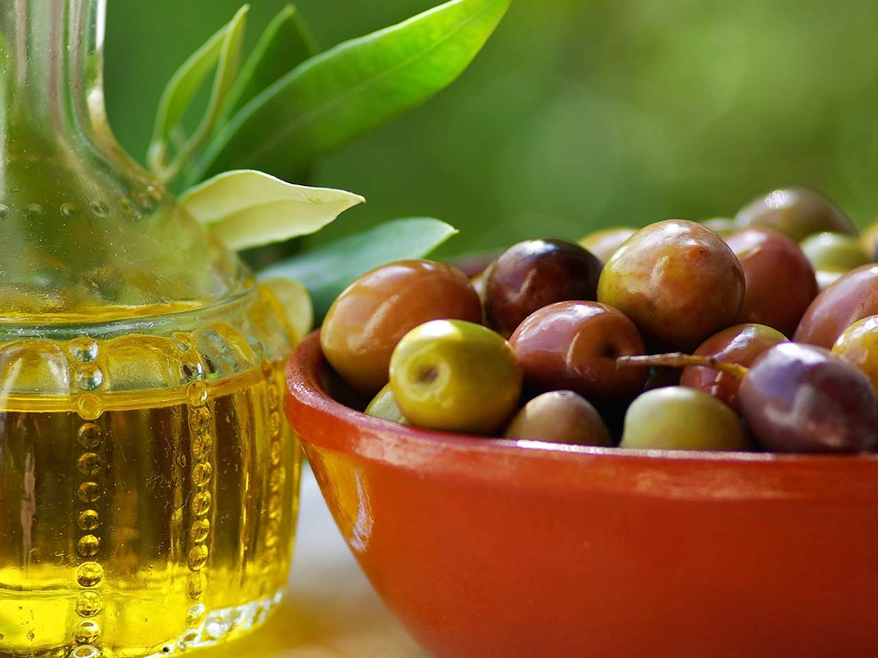 Bowl of olives and a bottle of olive oil